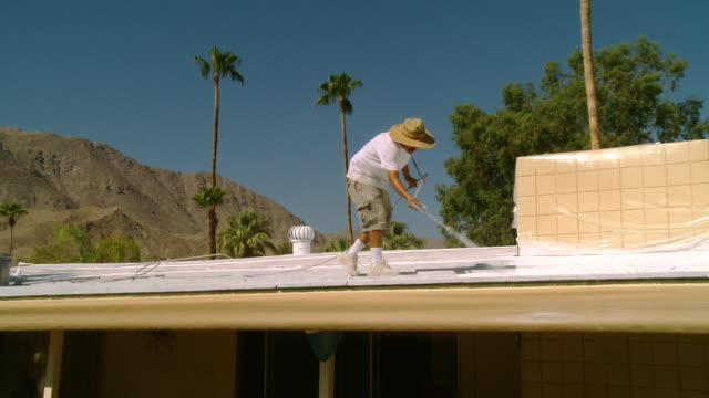 ws zi painter working on roof of house in desert surrounded by palm tree / rancho mirage, california, usa.   - 吹きかける点の映像素材/bロール