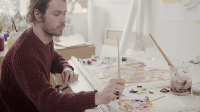 Painter works on abstract painting in art studio