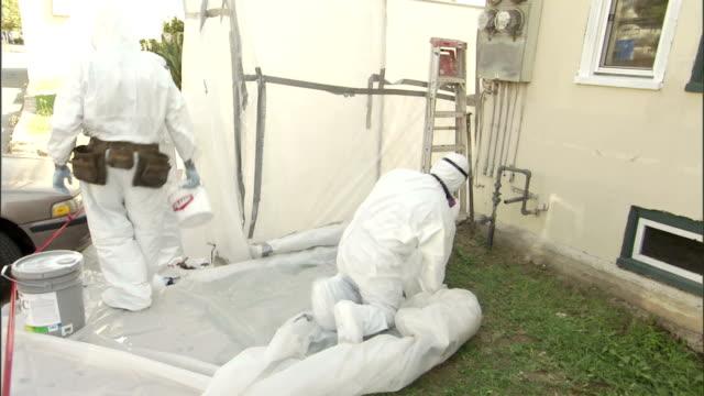 vídeos de stock e filmes b-roll de painters remove equipment and drop cloths from a front yard. - pano de protecção