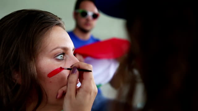 stockvideo's en b-roll-footage met painting face to sport supporter for the championship - verf