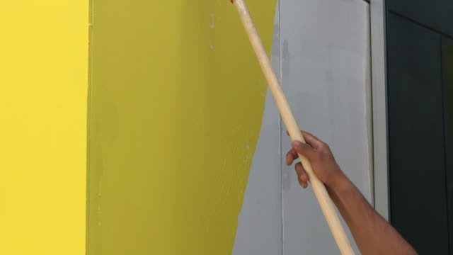 painting hand with paintbrush yellow - wall building feature stock videos & royalty-free footage