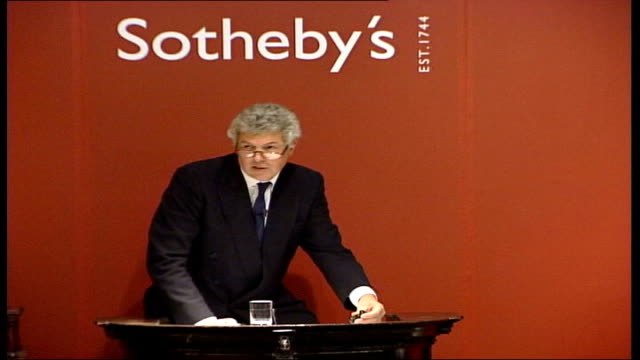 picture restorer discovers 'hidden' rembrandt tx sotheby's auctioneer announces sale of vermeer ' young woman at the virginals' for gbp 145 million... - sotheby's stock videos and b-roll footage