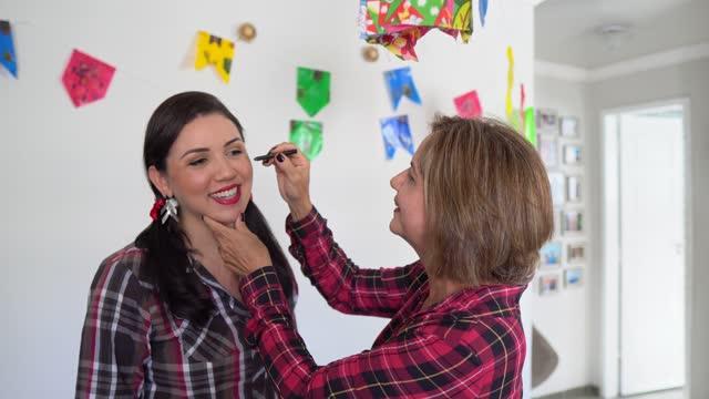 vídeos de stock e filmes b-roll de painting the face at the festa junina - dança quadrada