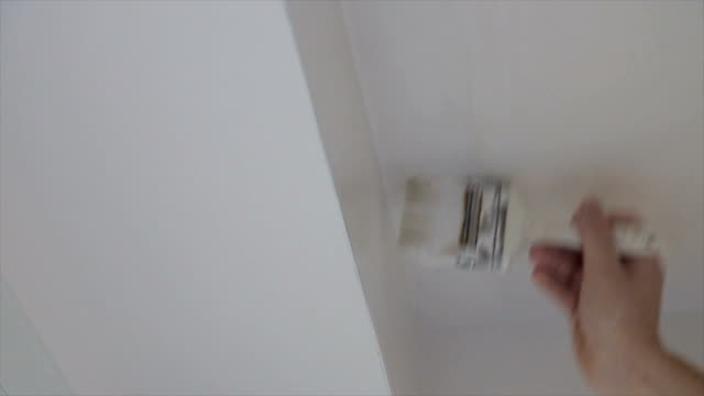 painting the wall in the white color.close up - paint roller stock videos & royalty-free footage