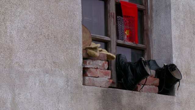 cu pair of black boots airing on window sill, traditional chinese red paper cut hanging on window, near taizhou, jiangsu, china - medium group of objects stock videos & royalty-free footage