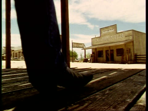vídeos de stock e filmes b-roll de pair of cowboy boots walk past and away from camera, left to right, western town, usa - peão papel humano