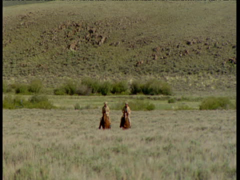 pair of cowboys approach camera on horseback, montana - recreational horseback riding stock videos & royalty-free footage