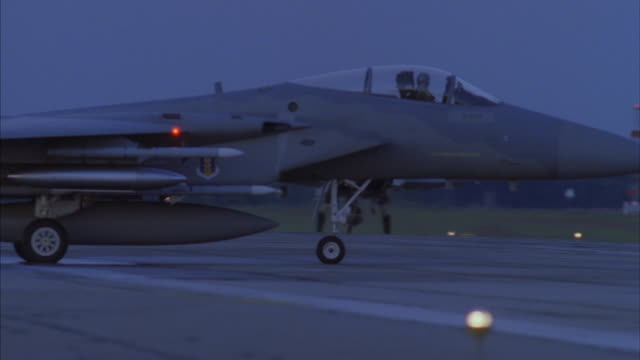 A pair of F-15 fighter jets is taxiing on an air force base runway as they are preparing for takeoff.