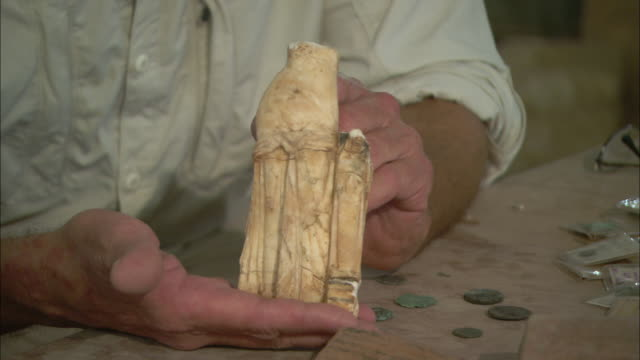 A pair of hands holds a damaged sculpture.