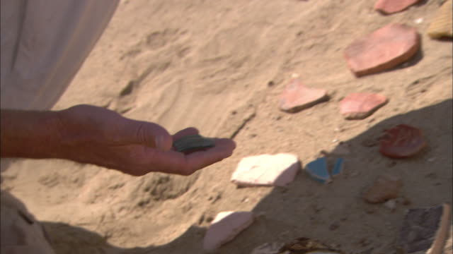 A pair of hands picks up shards of pottery and glass in a desert.