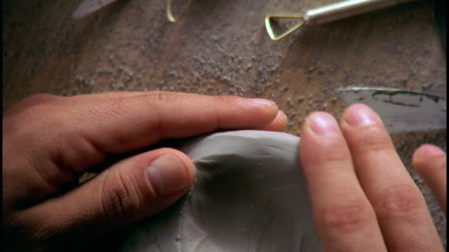 A pair of hands smooths a piece of clay.