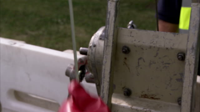 a pair of hands wearing red gloves pulls on a wire cable. available in hd. - pulley stock videos & royalty-free footage