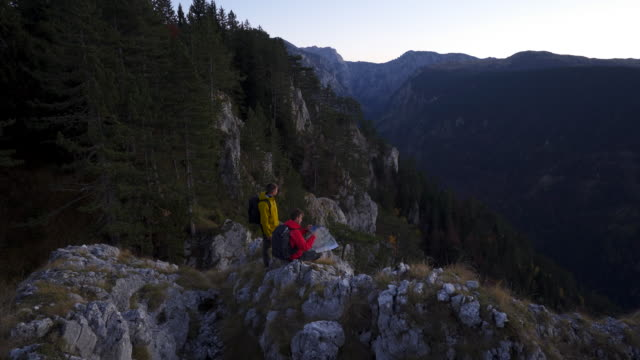 pair of hikers looking at a map cliffside at dusk - durmitor national park stock videos & royalty-free footage