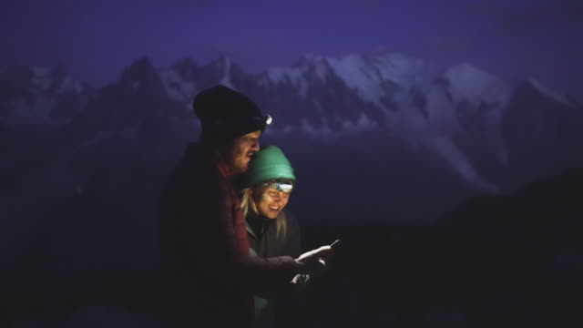 vídeos de stock, filmes e b-roll de pair of hikers looking at a phone at night in the mountains - lanterna elétrica