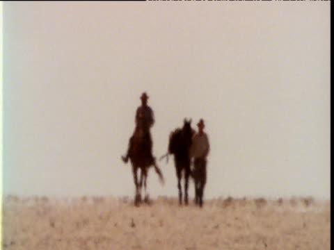 pair of horsemen cross scorching outback salt pan in heat haze, australia - hat stock videos & royalty-free footage