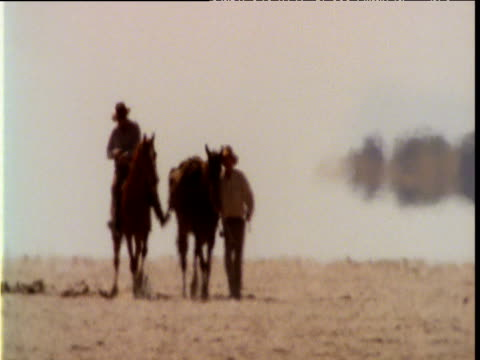 pair of horsemen cross scorching outback salt pan in heat haze, australia - hat stock videos and b-roll footage