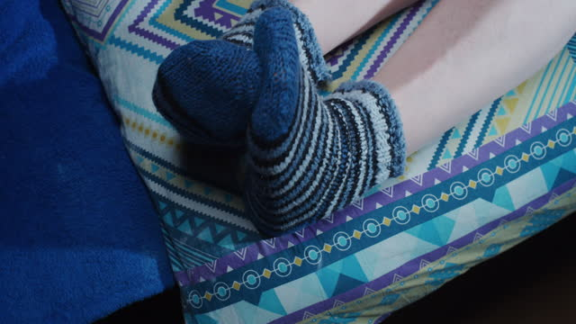 pair of human feet wearing wool socks moving in bed - pair stock videos & royalty-free footage