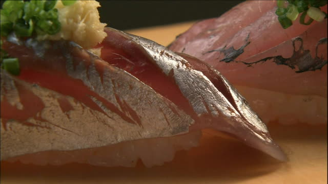 a pair of nigiri ovals lie on a counter top. - nigiri stock videos and b-roll footage