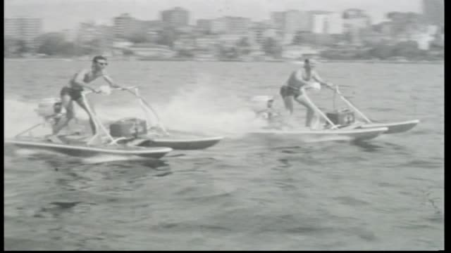 pair of personal twin hull jet skis with outboard motors pass men motor past standing on hulls holding handle bars sydney harbour bridge seen in bg - acquascooter video stock e b–roll