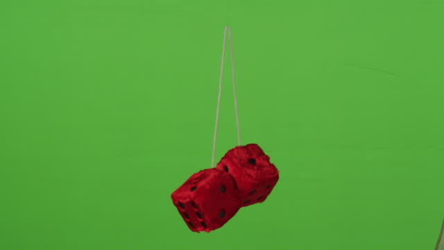 a pair of red fuzzy rearview mirror dice hang over a green screen background. - curiosity stock videos & royalty-free footage