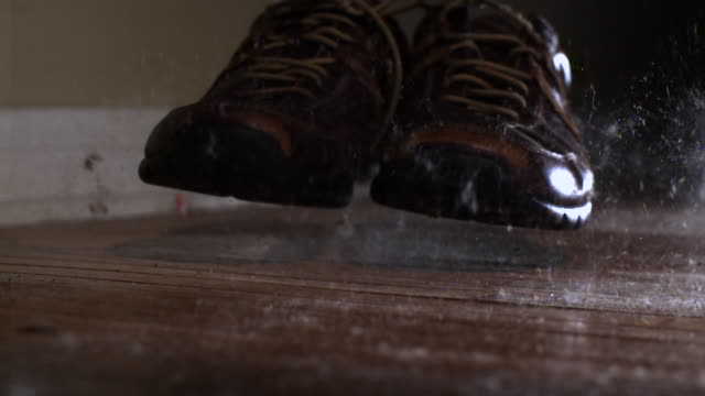 ms slo mo pair of shoes falling on dusty wooden floor - pair stock videos & royalty-free footage
