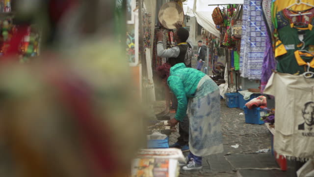 a pair of shoppers rummage through various wares displayed in a street market in cape town - cape town stock videos & royalty-free footage