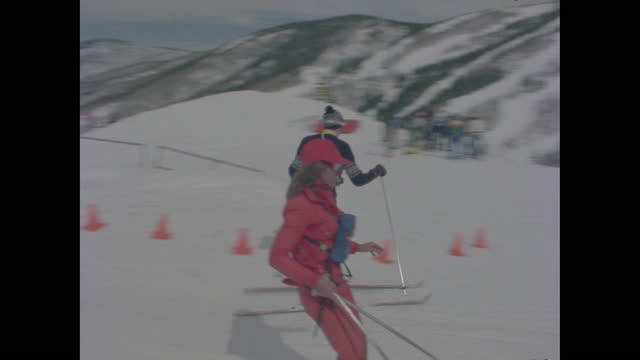 pair of skiers hops off lift chair at mountaintop and skiis to join group - ski resort stock videos & royalty-free footage