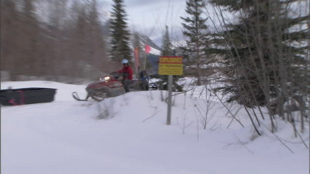 """stockvideo's en b-roll-footage met a pair of snowmobiles hauling equipment passes a sign reading, """"explosives no trespassing"""" on a snowy trail. - reddingswerker"""