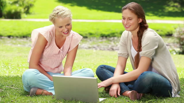 two women sit on the grass as they use a laptop together and then both look at the camera - gambe incrociate video stock e b–roll