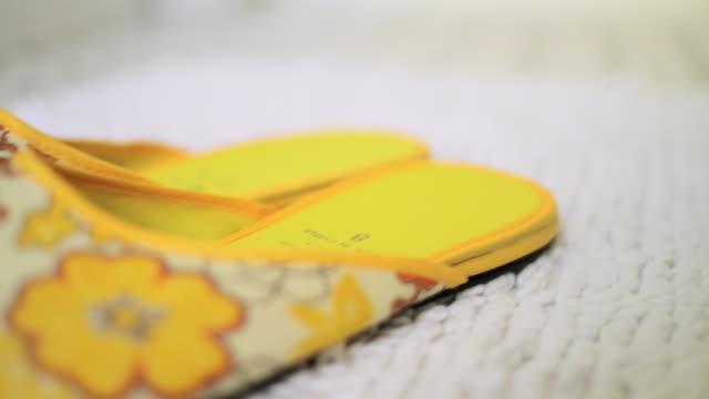 Pair of yellow slippers on bathroom floor
