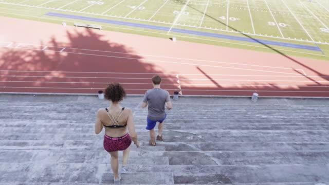vídeos de stock, filmes e b-roll de uhd 4k: par de jovens adultos atravessar o treinamento em um estádio juntos - competição