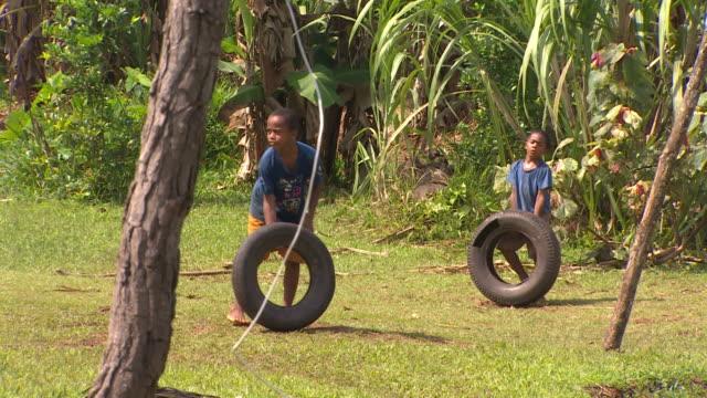 pair of young boys playing by rolling tyres in village of vunidogoloa, fiji. - partire bildbanksvideor och videomaterial från bakom kulisserna