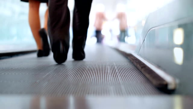 stockvideo's en b-roll-footage met pair on airport moving walkway - voetgangerspad