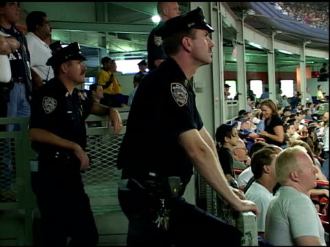 vídeos y material grabado en eventos de stock de pairs of policemen in uniform standing on security watch in bleachers, wearing american flags, chewing gum & looking at camera during first mlb... - 2001
