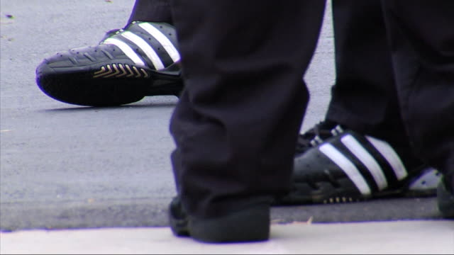 pairs of unidentifiable male feet in black athletic shoes, 2 adidas & 1 starter, performing stretching exercised on pavement. training, athlete,... - sports training drill stock videos & royalty-free footage