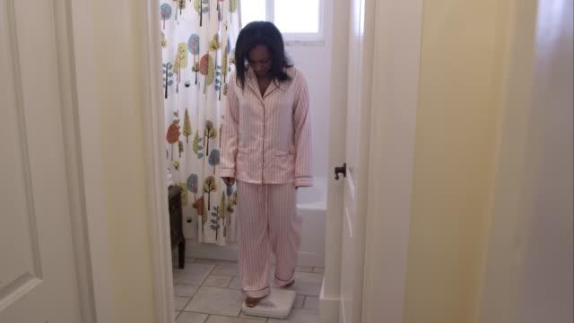 pajamaed woman in bathroom weighing herself. - 体重計点の映像素材/bロール