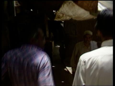 pakistan landi kotal la road sign pull back ms special police in street zoom in on afghan mountains in b/g gv tribal traders in street in heroin... - east stock videos & royalty-free footage
