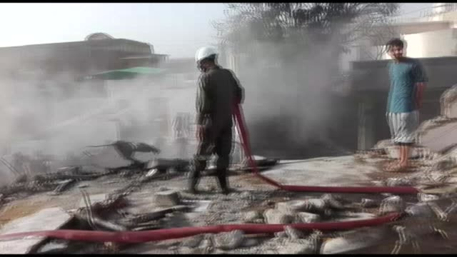 pakistani emergency workers flood the scene of a plane crash in the southern city of karachi - aerospace stock videos & royalty-free footage