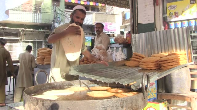 pakistani food sellers prepare specialities for ramadan in a market in rawalpindi as shoppers stock up on supplies for the month long muslim fasting... - fasting activity stock videos & royalty-free footage