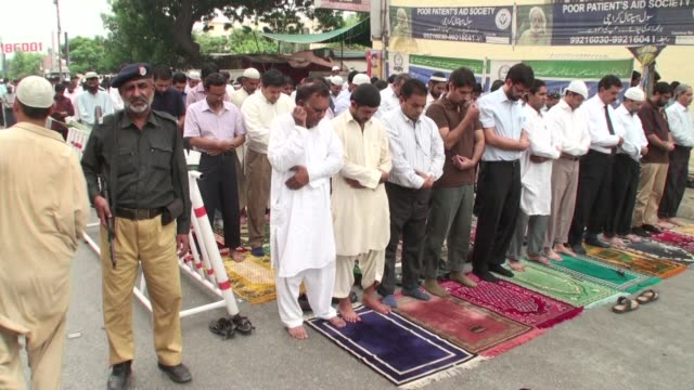 pakistani muslims offer friday prayer outside the local mosque at i i chundrigar road a financial district of karachi pakistan a pakistani policeman... - mosque stock videos & royalty-free footage