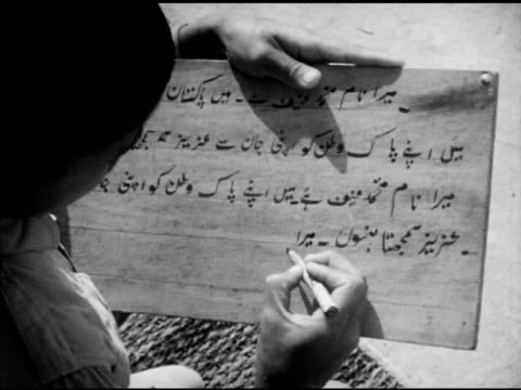 vídeos y material grabado en eventos de stock de pakistani people village boys holding slates sitting outdoors ots cu boy's slate w/ urdu script boy's fingers holding marker writing right to left vs... - pizarra roca metamórfica