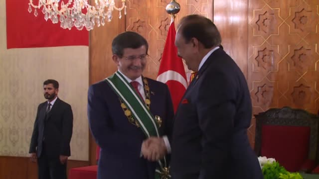 pakistani president mamnoon hussain honors turkish prime minister ahmet davutoglu with the order of pakistan during davutoglu's official visit in... - primo ministro turco video stock e b–roll