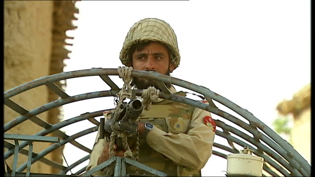 pakistani troops on patrol in afghan border region; pakistani troops and trucks on patrol / dug hole in ground / soldier with mounted rifle in back... - surrounding wall stock-videos und b-roll-filmmaterial