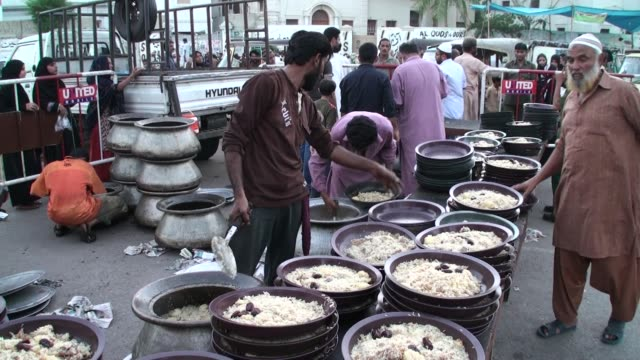 pakistani volunteers distribute iftar food among muslim devotees after they broke their fast during the muslim fasting month of ramadan at numaish... - mosque stock videos & royalty-free footage