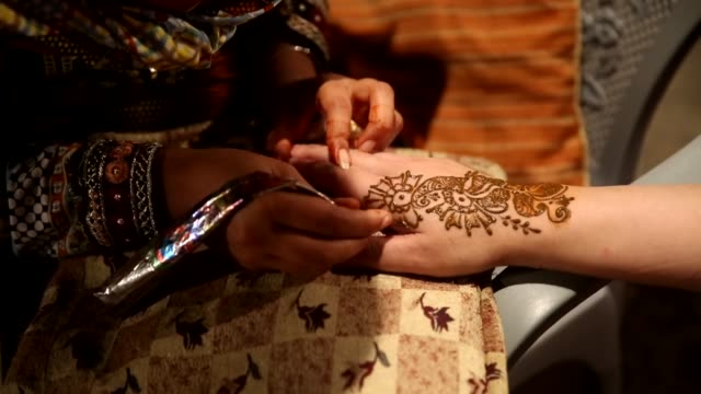 Pakistani women get their hands painted with henna ahead of the Eid al Fitr holiday which marks the end of the Muslim fasting month of Ramadan at a...