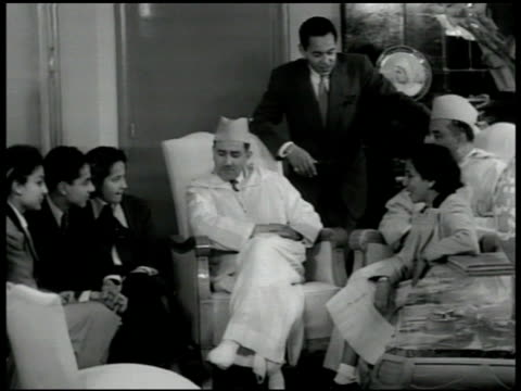 palace int palace room w/ sultan sidi muhammad v sitting w/ family talking w/ his son muhammad hassan standing by chair - 1951 stock videos and b-roll footage