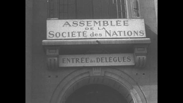 "palace of nations in geneva / sign above entrance to building that reads ""assemblee de la societe des nations"" / inside building, men speak at... - 外交点の映像素材/bロール"