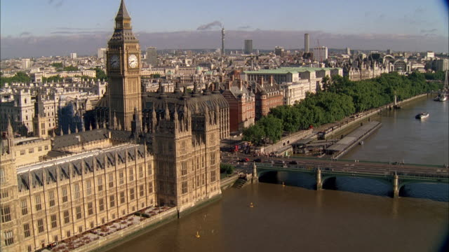 AERIAL Palace of Westminster Palace, Big Ben, the River Thames, and traffic crossing on the Westminster Bridge / London, England, United Kingdom