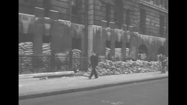 palace of westminster / workers on the premises / trucks and double-decker buses pass bush house / sandbags in basement of building / sandbags and... - parliament building stock-videos und b-roll-filmmaterial