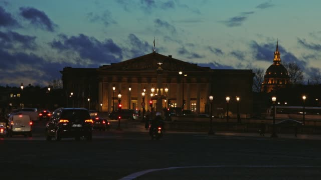 Palais Bourbon French National Assembly in Paris France with cars passing by by night Taken from Place de la Concorde